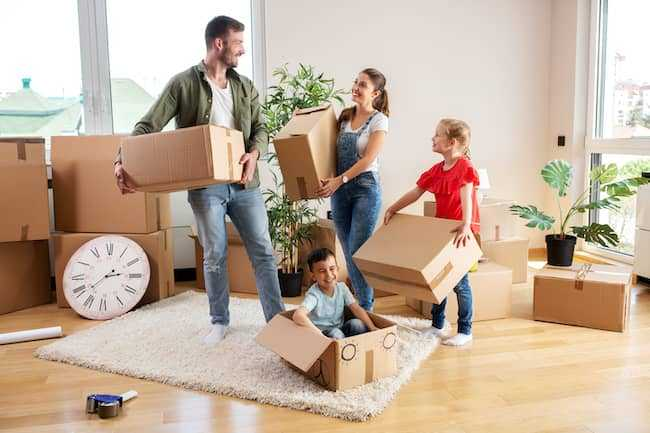 Family holding moving boxes in living room, smiling